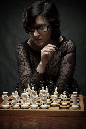 Pretty girl playing chess over dark background Stock Photo - 12163517