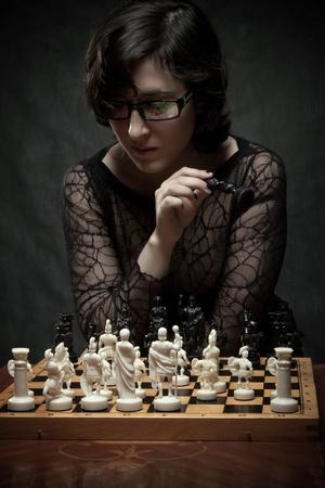 Pretty girl playing chess over dark background photo