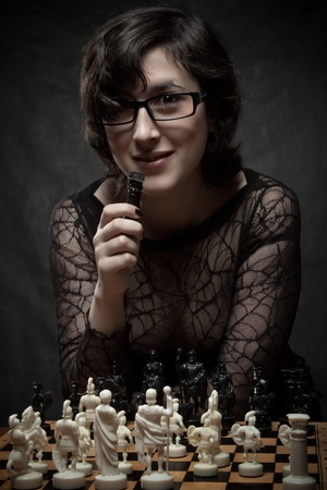 Pretty girl playing chess over dark background photo
