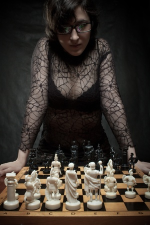 Pretty girl plyaing chess over dark photo