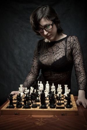 Pretty girl playing chess over dark background Stock Photo - 12163509