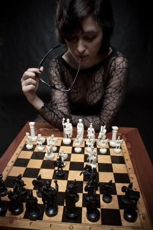 jugando ajedrez: Pretty girl jugando al ajedrez sobre fondo oscuro Foto de archivo
