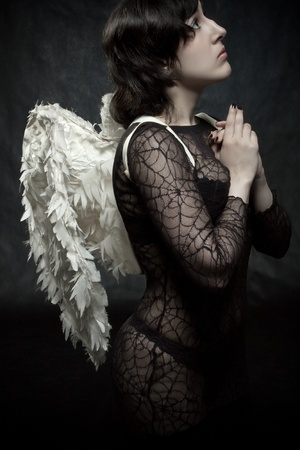 Pretty sexy angel praying over dark background photo