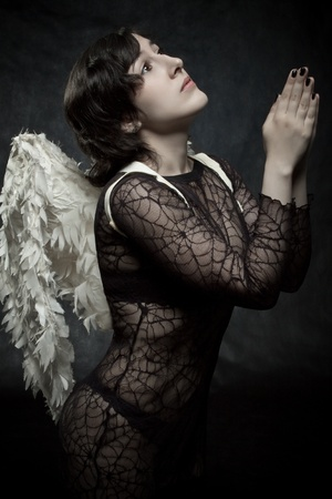 Sexy angel praying over dark background photo