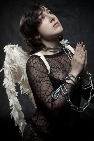 Pretty angel bonded by chains praying over dark Stock Photo - 12163513