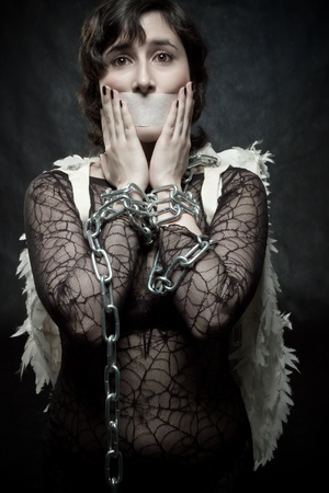 Pretty angel with sealed mouth and bounded hands posing ovre dark background photo