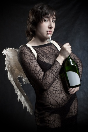 Pretty angel posing with cigarette and  bottle of wine over dark photo
