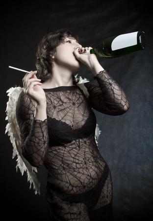 angel alone: Pretty angel with cigarette drinking wine over black