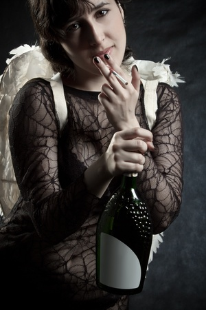 Pretty angel with cigarette and bottle wine posing over black photo