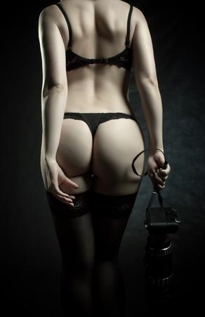 seductive: Pretty photographer with camera posing over dark background