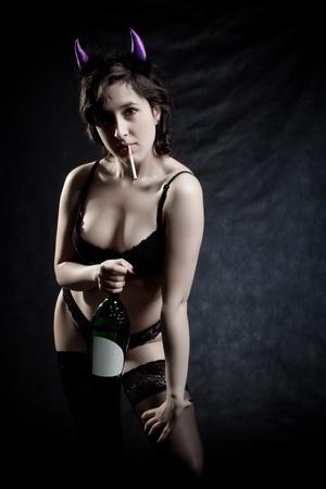 debauch: Pretty girl posing with bottle of wine over dark background