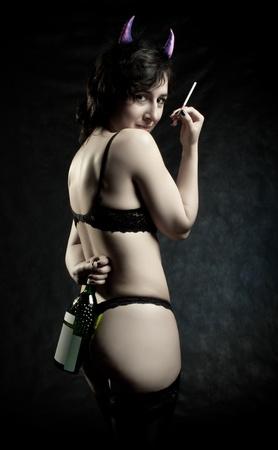 demon: Ładna dziewczyna z papieros i butelka wina pozowanie na ciemnym Zdjęcie Seryjne