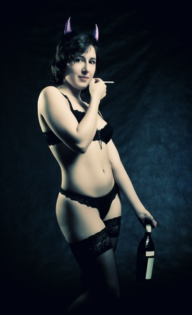 debauch: pretty sexy girl with horns, bottle of wine and cigarette posing over dark