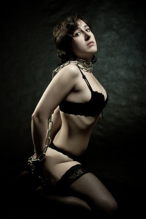 debauch: Pretty girl bounded by chains sitting on the floor over dark background