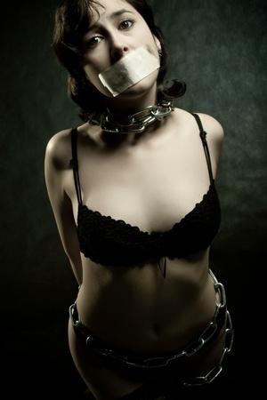gothic fetish: bounded pretty prisoner over dark background