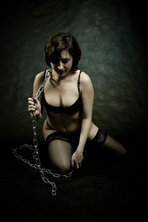 chained sexy pretty girl in underwear posing over dark background Stock Photo