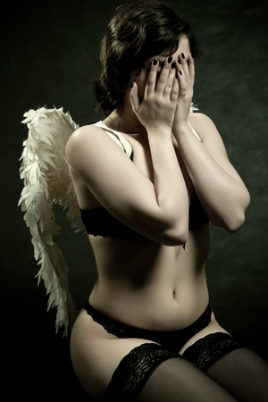 pretty angel in underwear posing over dark background photo