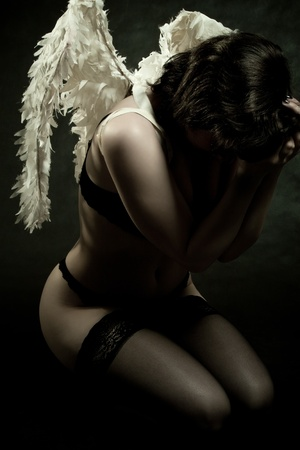 pretty angel posing over dark background Stock Photo