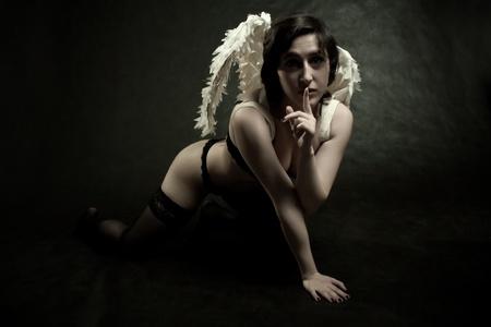 dark angel: pretty girl in underwear posing over dark background Stock Photo