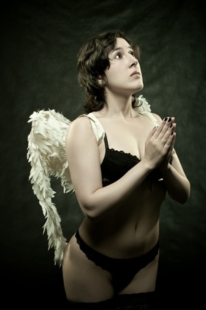 pretty sexu angel praying over dark background photo