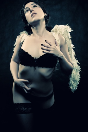 pretty sexu angel posing over dark background Stock Photo - 12162882