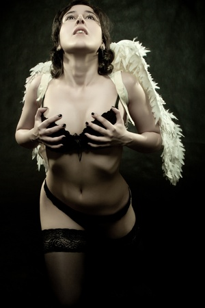 pretty sexy angel posing over dark background Stock Photo - 12162880