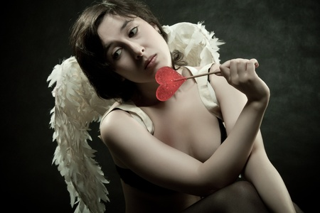 Sad pretty angel with lollipop photo