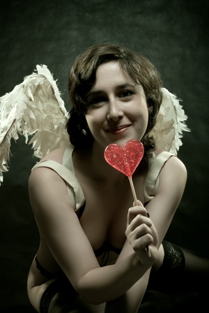 angel alone: Funny sexy angel posing with lollipop over dark background Stock Photo