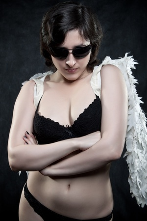 Pretty angel in glasses posing over dark background photo