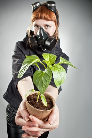 Redhead girl in respirator holding plant over gray. Focus on hands. photo