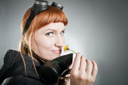 Redhead freckled girl with respirator holding dandelion over gray photo