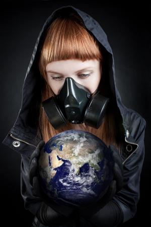 Girl in hood holding earth in her hands over dark background.  photo