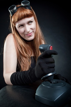 Redhead girl playing game with joystick over dark photo