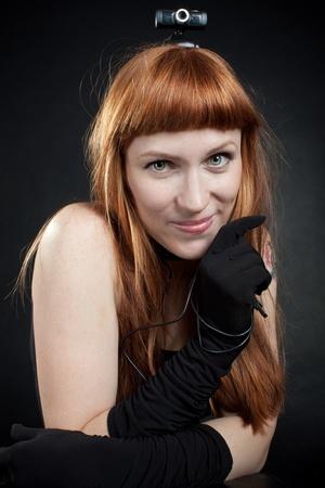 msn: Funny redhead girl with webcamera posing over dark Stock Photo