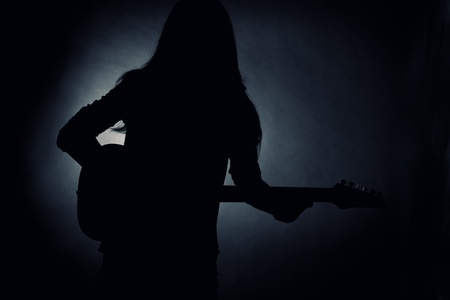 Silhouette of young man with long hair playing electrical guitar  Stock Photo - 12163715