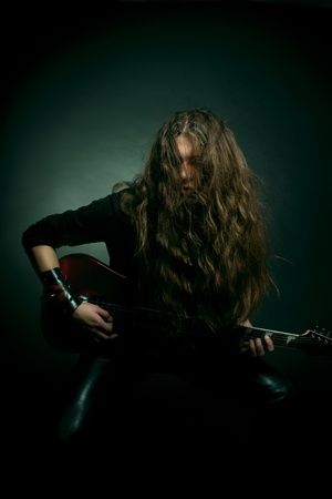 Young man with long hair playing electrical guitar over dark background Stock Photo - 12163741