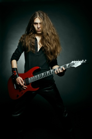 Young man with long hair playing electrical guitar over dark background Stock Photo - 12163754