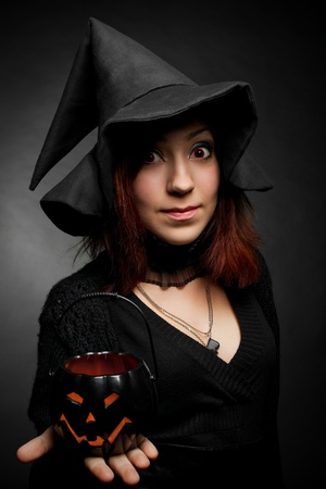 Pretty witch in hat posing over dark with pumpkin in hand photo