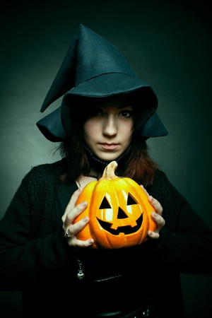 Pretty witch in hat posing over dark with pumpkin in her hands Stock Photo - 12163777
