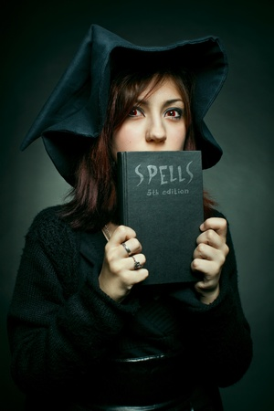 Pretty red-eyed young witch with spells book over dark Stock Photo - 12163789