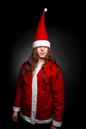 Long-haired young guy in santa costume posing over dark photo