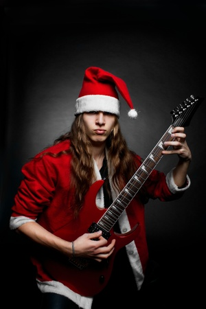 Guitarist clothed ing santa costume with red guitar playing over dark photo