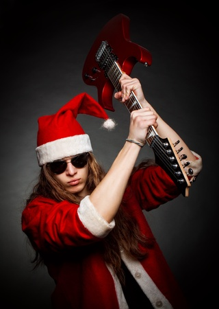 Crazy Santa posing with electric guitar over dark background photo