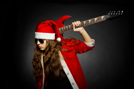 Santa with electric guitar posing over dark photo