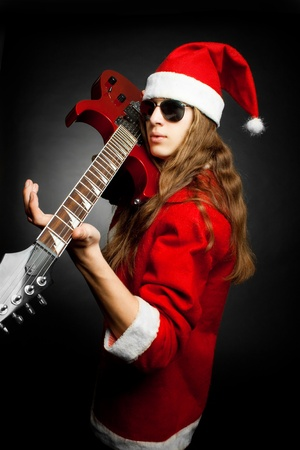 Young Santa Claus with red electric guitar posing over dark background photo
