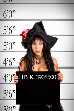 Mugshot of pretty witch in police station photo