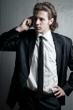 Joven empresario con teléfono móvil posando sobre fondo rayado Foto de archivo - 12163890