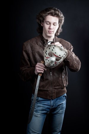 Handsome maniac with mask and machete in hands posing over dark background Stock Photo - 12163780