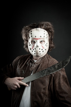 maniac: maniac in mask and machete in his hand posing over dark background
