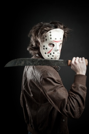 maniac in mask and machete in his hand posing over dark background Stock Photo - 12163781